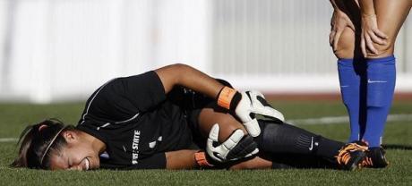 Soccer goalie on ground in pain holding knee