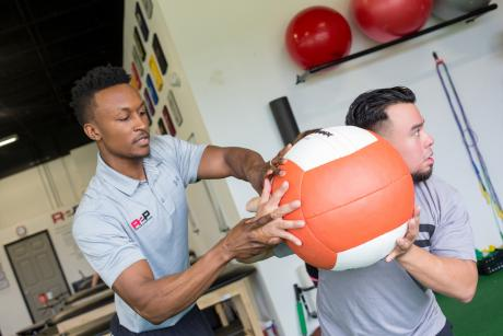 man teaching medicine ball throws to patient