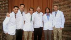 man with white coat and classmates