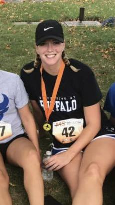 young woman sitting wearing medal after completing a 5K